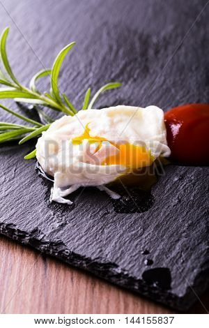 Single Poached Egg On Slate Stone With Herb And Ketchup