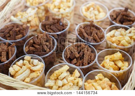 Croutons snack in plastic cups for party. Party snack lunch. Croutons crackers of white and brown whole grain bread. Many, plenty of beer snack.