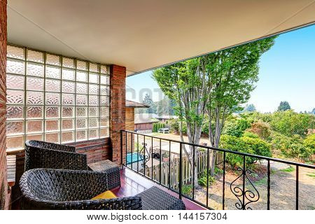 Balcony With Wrought Iron Railing And Black Wicker Chairs