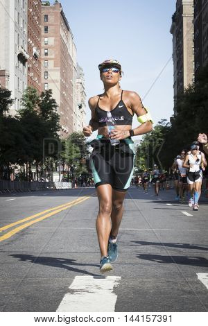 NEW YORK -?? JUL 24 2016: Athlete running the 10k portion of the NYC Triathlon Race on West 72nd St. The Panasonic New York City Triathlon is the only International Distance triathlon in New York City.