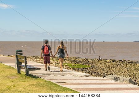Young couple walking at boardwalk in a summer day at Pocitos neighborhood in Montevideo Uruguay