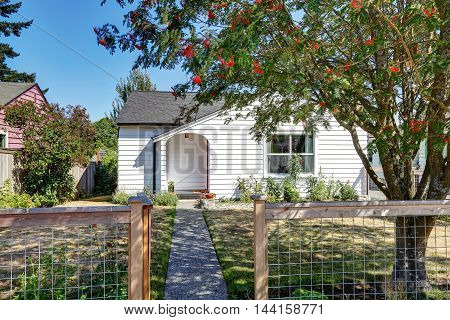 Small White Rambler House With Concrete Walkway.