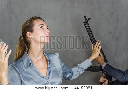 Beautiful girl in danger, and the man's hand with a gun threatens action on a gray background