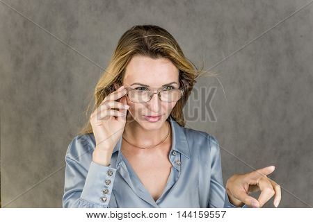 The girl points a finger action on a gray background