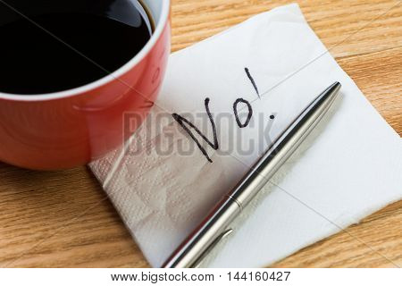 Coffee cup pen and napkin with words on wooden table