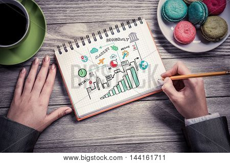 Top view of female hands drawing business strategy in notebook