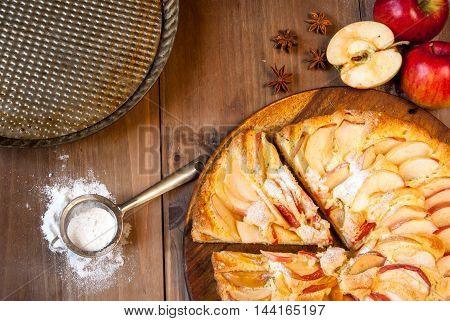 Traditional apple pie on a wooden table, with apple and powdered sugar, top view