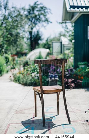 view of old wooden chair on painted hopscotch on asphalt against of sunny garden.