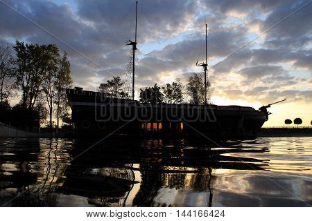 Old masted wooden galeon ship moored at dock in the sea bay stock image