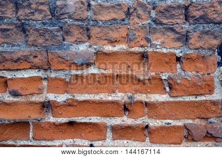 Old weathered brick wall fragment. Cracked concrete vintage brick wall background