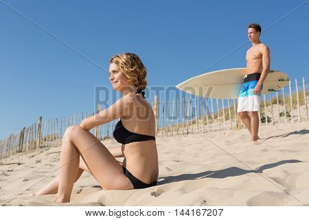 male surfeur and his girlfriend on the beach