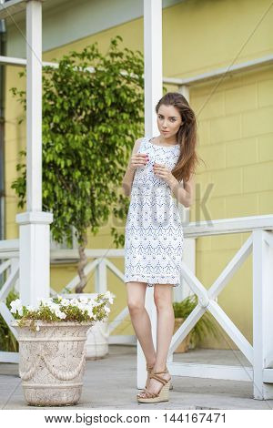 Young beautiful brunette woman in white dress