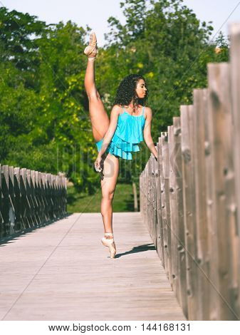 Latin dancer with leg raised above his head on the bridge of a park