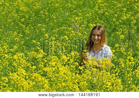 Beautiful smiling girl with ears of corn in hands on flowering rapeseed field