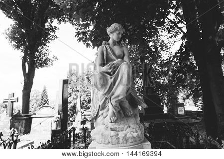 Catholic statue in the Gothic style in the cemetery, Shallow focus.