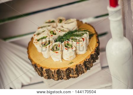 Wraps roll with spinach meat and paprika on wooden stump