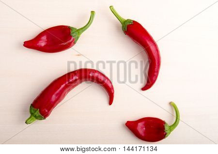 Top view of hot chili peppers on a light wooden board closeup