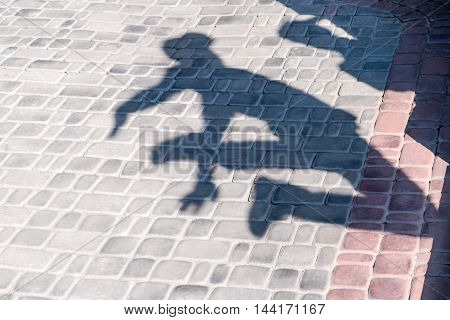 Shadow jumping man in a cap on stone blocks