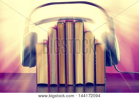 Books and headphones as an audiobook concept on a wooden table on a pink background. The sun's rays create a joyful mood