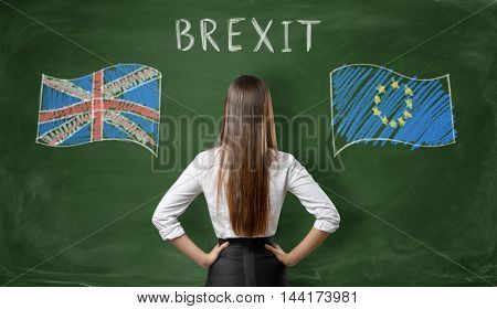 Back view of a businesswoman standing on a background of a blackboard with UK and EU flags on both sides with 'brexit' word above. British withdrawal. Significant decision. Substantial choice.