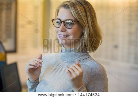 Young woman trying on glasses at the optician