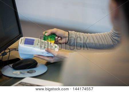 Optician and customer paying for your glasses