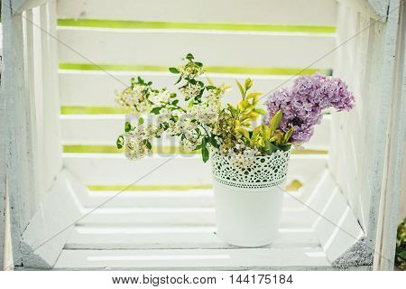Flowers in a white pot in white wooden box.