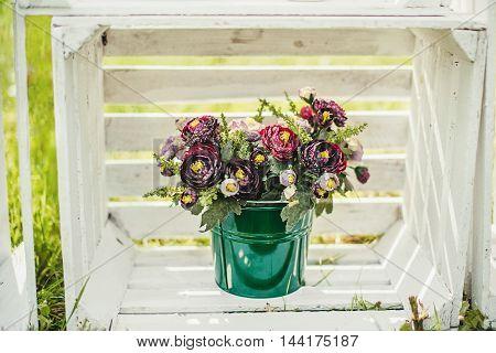Flowers in a green bucket in white wooden box