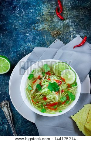 Chiсken soup with vegetable marrow  noodles in white bowl. Blue background. Selective focus.