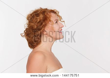 Closeup profile of happy mature woman smiling and looking upwards. Beautiful red haired lady posing isolated on white background in studio.