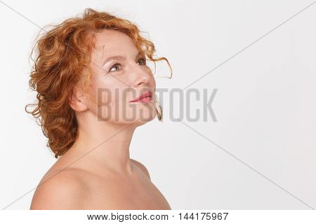 Portrait of happy mature woman thinking about something. Thoughtful senior or middle aged woman posing isolated on white in studio.