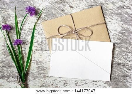 bouquet of purple wildflowers with blank white greeting card and envelope with copy space on whithe wooden background