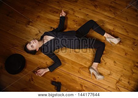Woman In A Black Suit With Gun Lying On The Floor
