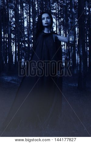 Beautiful Brunette Woman In Black Dress And Black Cloak In The Magic Forest