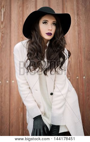 Beautiful Fashionable Smiling Woman In A Black Hat And White Coat Posing Outdoors Near The Gate