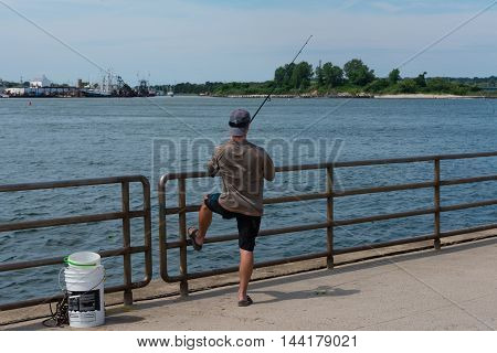 Fisherman's Cove Manasquan NJ USA-- August 24 2016 -- Lone fisherman casting with a rod and reel at Fisherman's Cove in Manasquan NJ. Editorial Use Only
