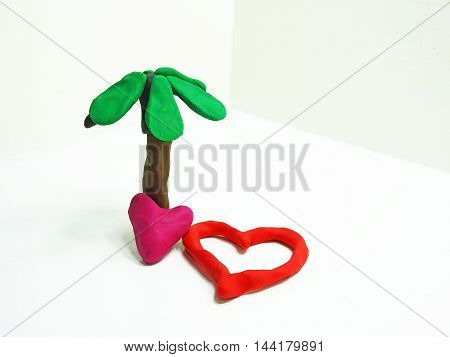 Two red hearths made from plasticine. Isolated on white background.