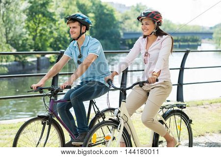 Young Smiling Couple On Bicycles Ride In The Park