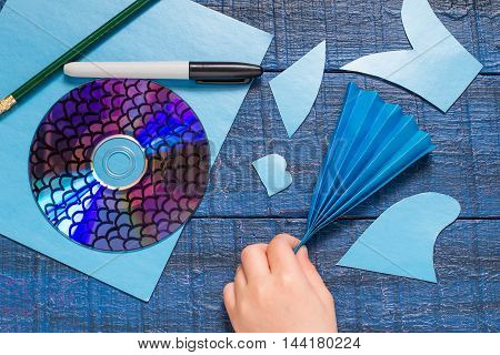 Making homemade toy fish from the CD. Paper CD pencil marker on blue wooden table. Handmade children's project. Step by step photo instructions. Step 6: The child folded paper in form of fan
