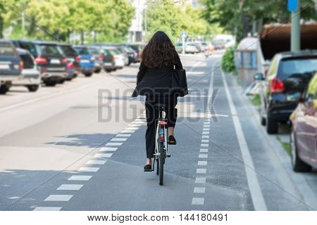 Rear View Of A Young Businesswoman Riding Bicycle On Street