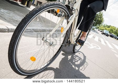 Low Section Of Businesswoman Riding Bicycle On Street