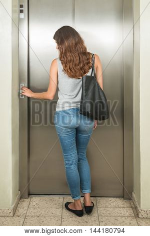 Rear View Of A Young Woman With Handbag Using Elevator