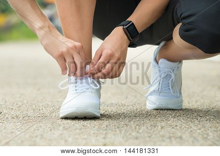 Close-up Of Female Athlete Trying Running Shoes Getting Ready For Jogging