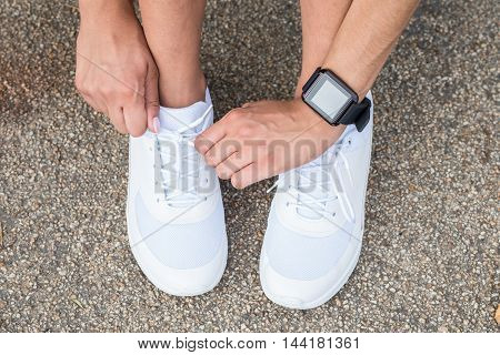 Close-up Photo Of Woman Tying Jogging Shoes