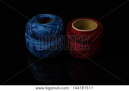 Low key photo of threads with black background