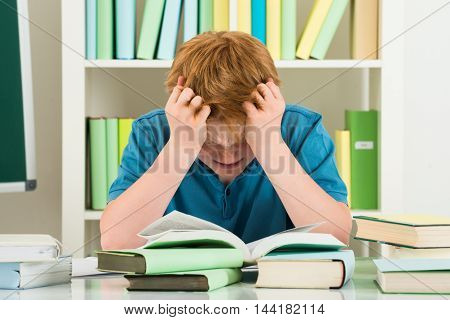 Exhausted Boy Studying In Library With Books On Desk