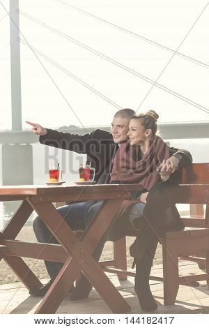 Couple in love sitting in an outdoor cafe by the river on an autumn sunny day drinking tea hugging and relaxing