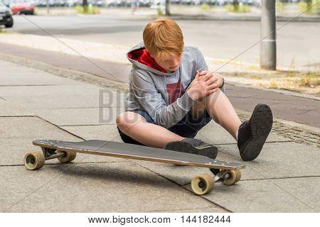 Boy Looking At His Injured Leg Sitting Near Skateboard