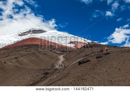 Cotopaxi volcano with some climbers ascending by its sandbanks