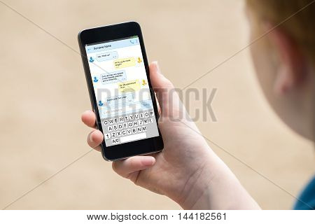 Boy's Hand Holding Mobile Phone With Messages On Screen